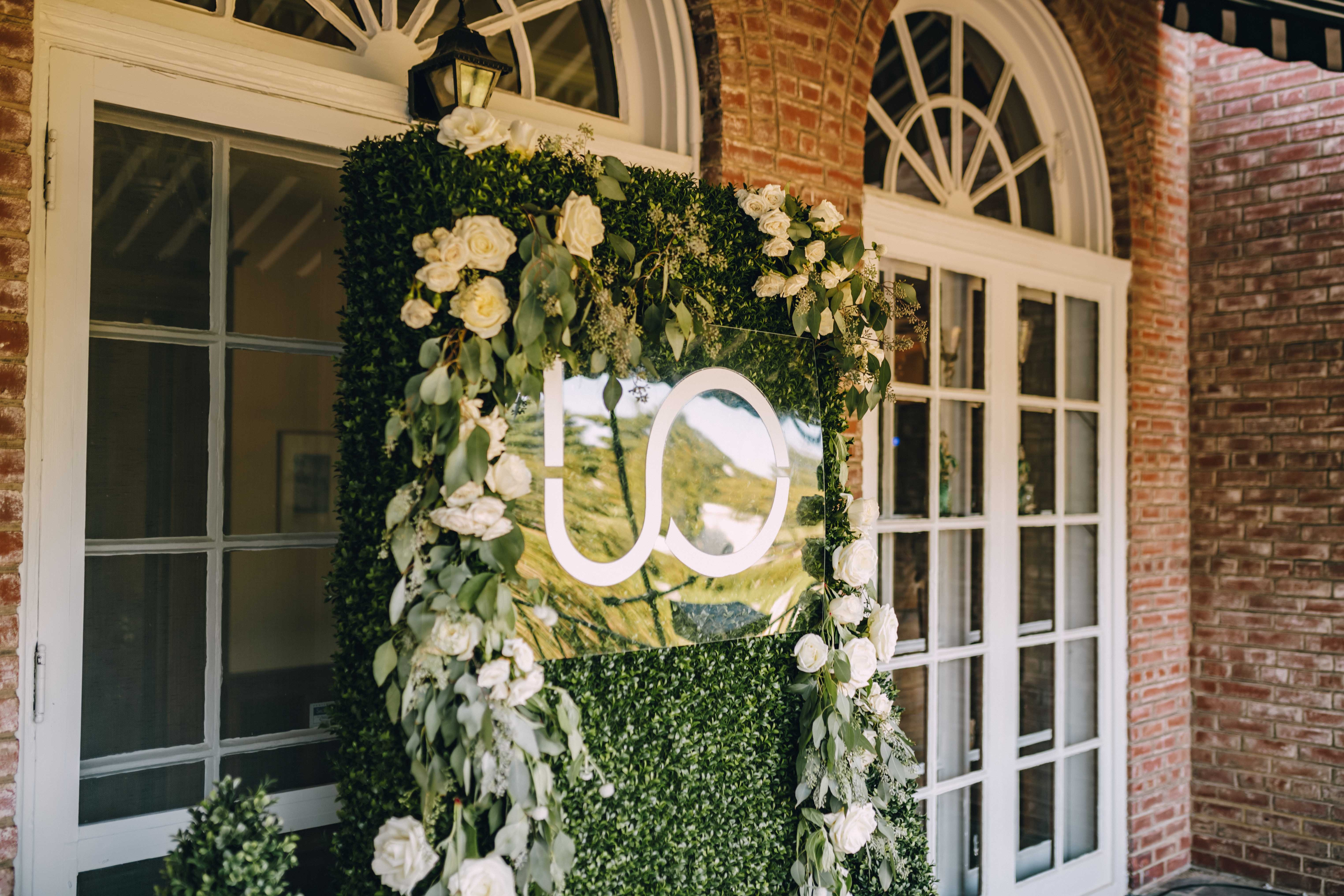 Green foilage backdrop with Upton Oxmoor Logo